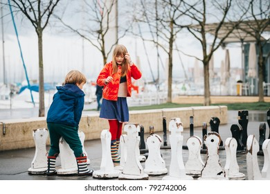 Group of two kids playing giant chess on playground, wearing rain coats and boots. Image taken in Ouchy, Lausanne, Switzerland