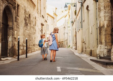 Group of two kids walking on the streets of old european town, wearing backpacks. Travel with children. Back view