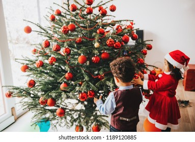 Group of two little children playing with Christmas tree at home