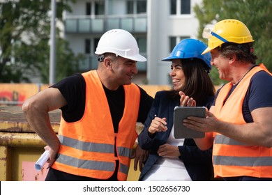 Group of two male and and one female workers on construction site