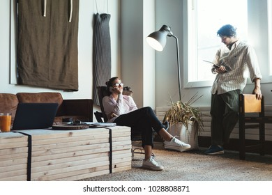 Group of two people with laptops in small loft office. Man and woman working together, talking on the phone
