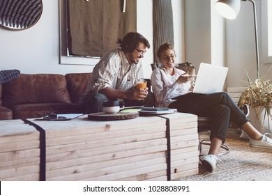 Group of two people with laptops in small loft office. Man and woman working together. Good new ideas