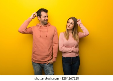 Group of two people on yellow background having doubts while scratching head