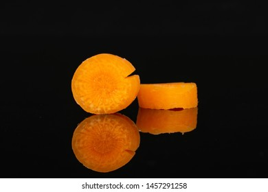 Group of two slices of peeled orange baby cut carrot isolated on black glass