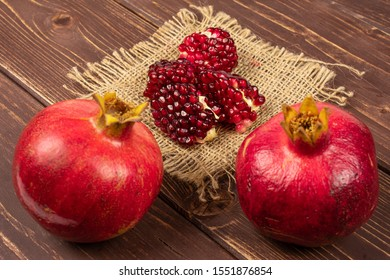 Group of two whole four pieces of fresh red pomegranate on natural sackcloth on brown wood