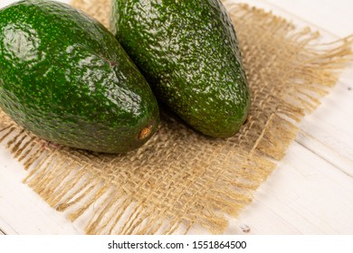Group of two whole fresh green avocado on natural sackcloth on white wood