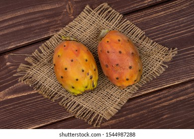 Group of two whole fresh orange opuntia on natural sackcloth flatlay on brown wood