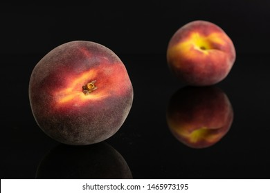Group of two whole fresh red peach one is in the front isolated on black glass
