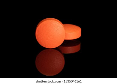 Group of two whole orange tablet pharmacy isolated on black glass