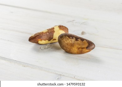Group of two whole unshelled brazil nut on white wood