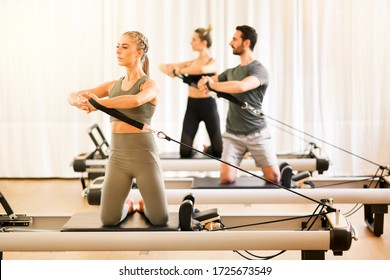 Group of two women and a man doing torsion rotation exercises during a class using pilates reformer beds in a high key gym with copy space in an active lifestyle and fitness concept