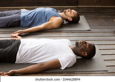 Group of two young afro american and caucasian sporty people practicing yoga lesson lying in Dead Body or Corpse pose, Savasana exercise, working out, resting after practice, indoor close up, studio