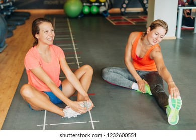 Group of two young fit women warming up in sport gym club