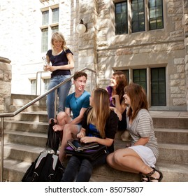 Group of university or college students sitting on steps, visiting and having fun