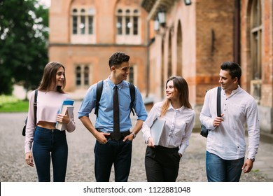 Group of university students with books in college campus discussing on the road.