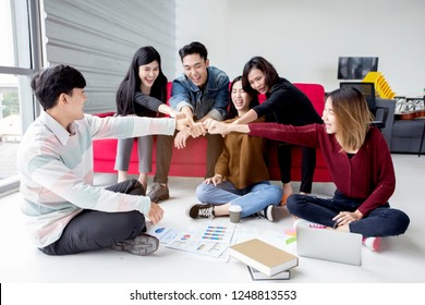 Group Of University Students doing homework and join hand together  helping report each other sitting on floor and sofa at apartment