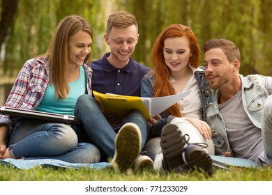 Group of university students sitting on the grass studying together outdoors at the campus communication education teamwork homework brainstorming teenage diversity togetherness friends