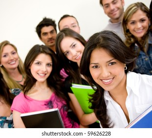 Group of university students smiling and holding notebooks
