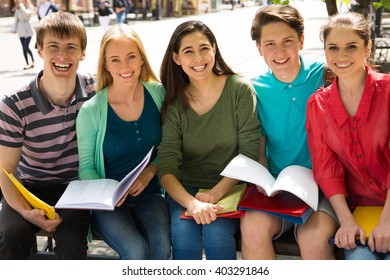 Group of university students studying, reviewing homework in park