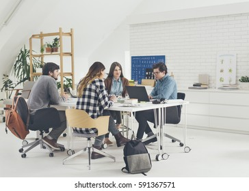 Group of university students studying together in classroom.