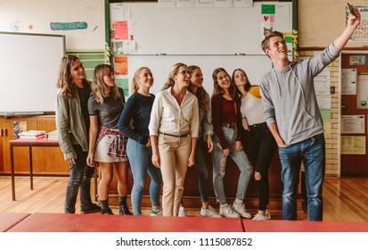 Group of university students with teacher making a selfie, Young people with professor in lecture room taking selfie with mobile phone.