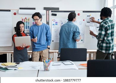 Group of university students is writing on a whiteboard and talking while their group mates discussing something and looking at the laptop screen. Studying at web design faculty concept