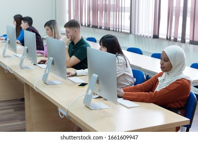 Group of  university IT technologies students working on practice lessons. Sitting near therir computer and looking for solution during class.