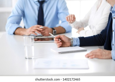 Group of unknown business people discussing questions at meeting in modern office, close-up of hands. Managers at negotiation or brainstorm. Teamwork, partnership and business concept