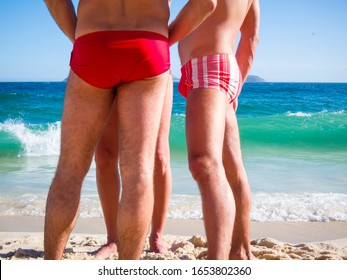 "A group of unrecognizable Brazilian men wearing a style of swimwear known locally as ""sunga"" standing on the shore of Ipanema Beach in Rio de Janeiro, Brazil"