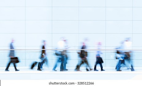 Group of unrecognizable business people in front of a wall, blurred motion, copy space above the people