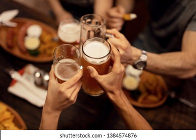 Group of unrecognizable friends  celebrating and toasting with beer while having lunch in a tavern.