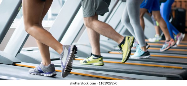 Group of unrecognizable people exercising at the gym running on the treadmills.