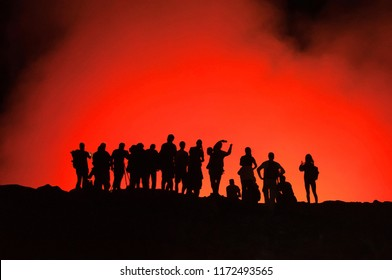 Group of unrecognized silhouettes of people standing on the edge of Erta Ale Volcano, illuminated with red lava smoke, Danakil Depression, Ethiopia, Adventure travel in Africa
