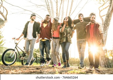 Group of urban friends gang walking in city skate park with backlighting at sunset - Youth and friendship concept with multiracial young people having fun together - Warm bright filter with soft focus