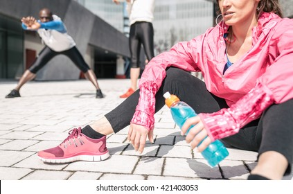 Group of urban runners making sport in an urban area. Focus on a girl holding a power drink. Concept about sport