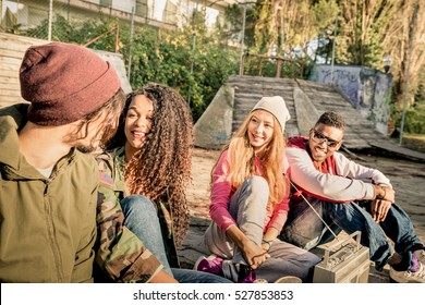 Group of urban style friends having fun time out at skate bmx park - Youth friendship concept with people together outdoors - Focus on african american young woman - Desaturated contrasted filter