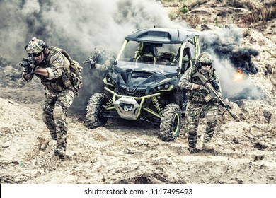 Group of US army infantries arriving on battlefield on patrol vehicle, moving forward and attacking enemy under cover of smokescreen in desert area. Special forces troops teamwork in combat conditions