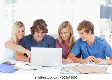 As the group use the laptop a female student points at the screen showing the something