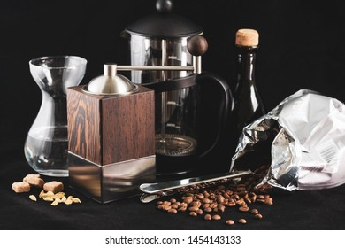 group of utensils for coffee preparation on black background. Modern hand-operated stylish coffee grinder, percolator, coffee beans poured out of bag, water in glass flask, brown sugar and cardamom