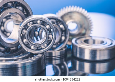 Group of various ball bearings and gears close up on nice blue background with reflections