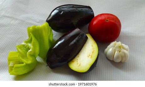 A group of vegetables with garlic, tomato, eggplants and bellpepper.
