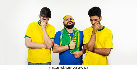 Group of very sad football fans isolated on white background