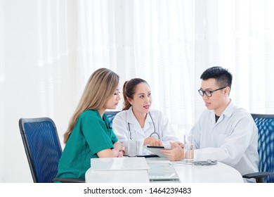Group of Vietnamese doctors gathered at table to discuss article on new innovative treatment on tablet computer