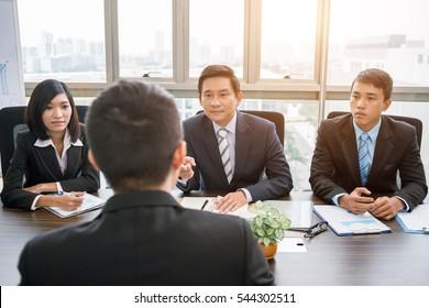 Group of Vietnamese investors having meeting with businessman