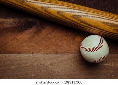A group of vintage baseball equipment, bats baseballs on wooden background