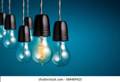 Group of vintage bulb lights with One antique Light bulb turn on , creative idea and leadership concept background.