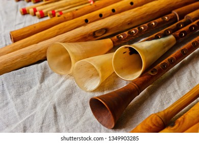Group of vintage medieval alphorn and reedpipe musical instruments made of wood and animal horns on a table covered with canvas cloth