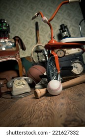 Group of vintage objects on attic hardwood floor, including old toys, phone and sports items.