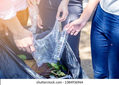 Group of volunteer Hands putting recycling waste bit to Black garbage bag collection in park .Environmental CSR Corporate social responsibility and reduce global warming concept