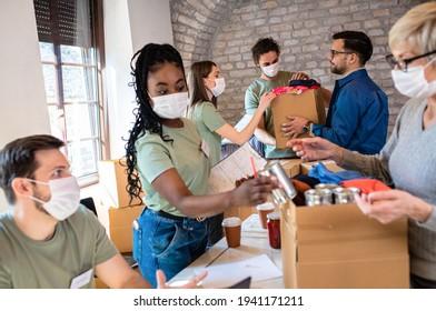 Gruppe von Freiwilligen mit Gesichtsmaske, die in gemeinnützigen Spendenzentren arbeiten.